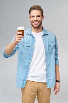 Portrait de jeune homme caucasien beau en chemise de jeans tenant une tasse de café pour aller