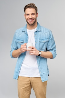 Portrait de jeune homme caucasien beau en chemise de jeans tenant une tasse de café