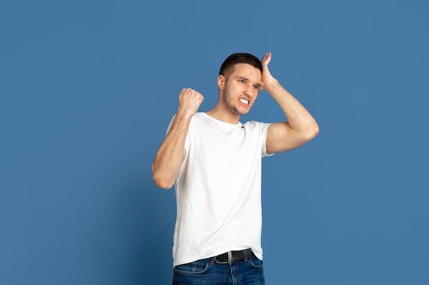 Portrait de jeune homme caucasien sur bleu