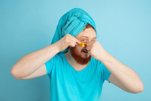 Portrait de jeune homme caucasien dans sa journée de beauté et routine de soins de la peau. modèle masculin aux cheveux roux naturels appliquant des patchs dorés sous les yeux.