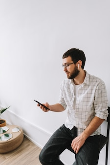 Portrait de jeune homme caucasien joyeux dans des verres et des écouteurs à l'aide de téléphone mobile.