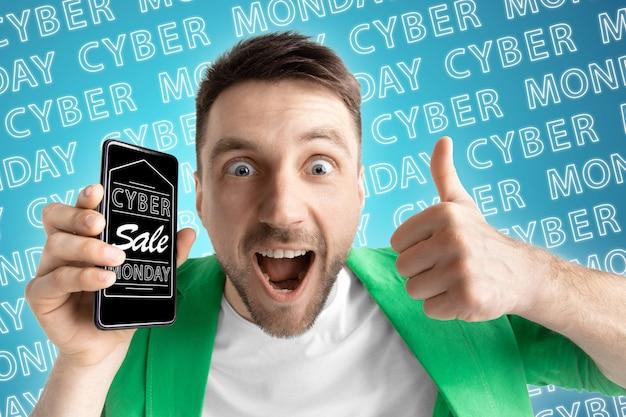 Portrait de jeune homme caucasien montrant l'écran du téléphone portable sur fond bleu avec lettrage néon. concept de vente, vendredi noir, cyber lundi, finance, entreprise. boutiques en ligne et facture de paiements.
