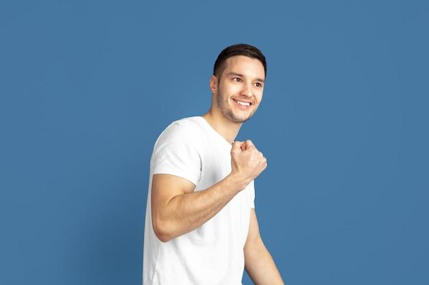 Portrait de jeune homme caucasien sur mur bleu