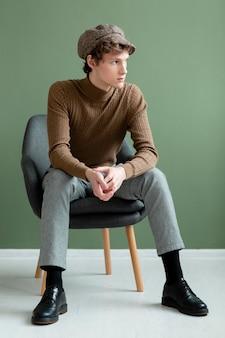 Portrait jeune homme avec chapeau assis sur une chaise