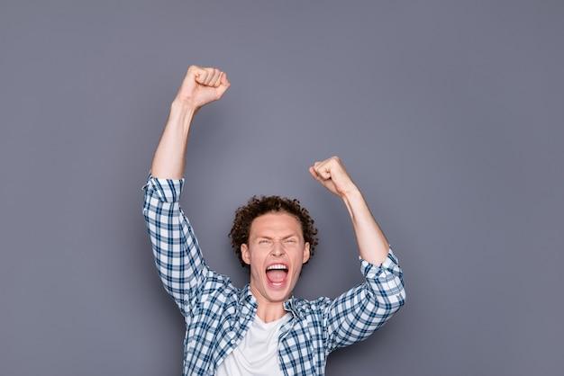Portrait de jeune homme en chemise à carreaux décontractée levant les mains en gagnant