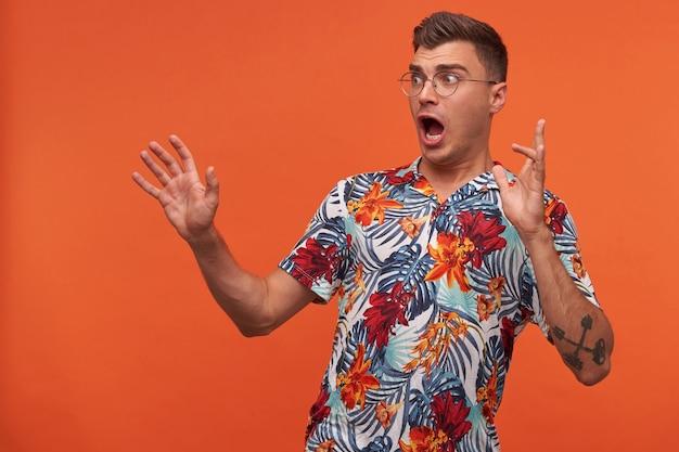 Portrait de jeune homme en chemise à fleurs avec la bouche ouverte se dresse sur le fond orange, levant les mains, regardant ailleurs, portant des lunettes, étant étonné