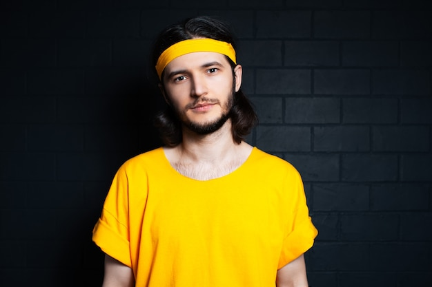 Portrait de jeune homme en chemise jaune sur fond de mur de briques noires.