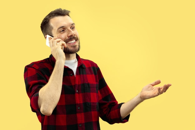 Portrait de jeune homme en chemise. vue de face. couleurs à la mode. parler au téléphone.