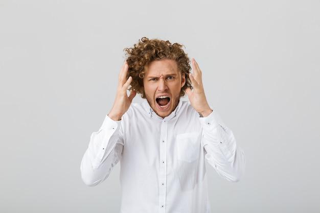 Portrait d'un jeune homme en colère aux cheveux bouclés
