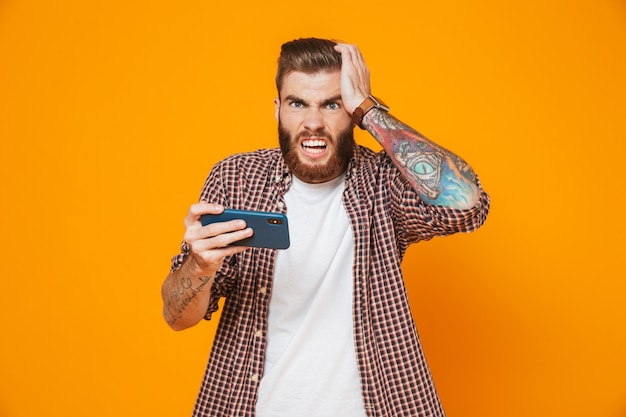 Portrait d'un jeune homme en colère portant des vêtements décontractés jouant à des jeux sur téléphone mobile