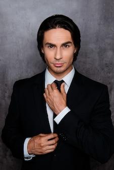 Portrait de jeune homme confiant corrigeant sa cravate noire