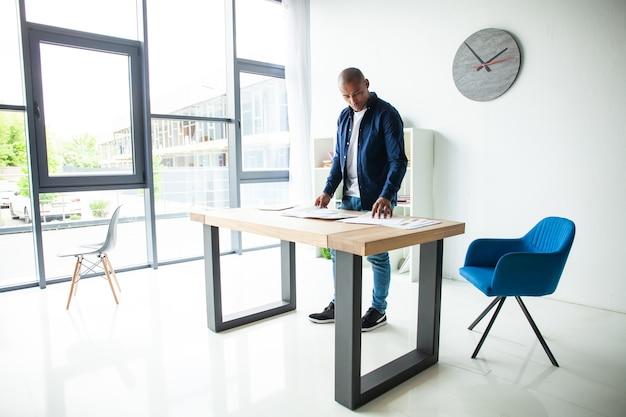 Portrait de jeune homme confiant debout à son bureau avec ordinateur portable. homme d'affaires africain travaillant dans un bureau moderne.