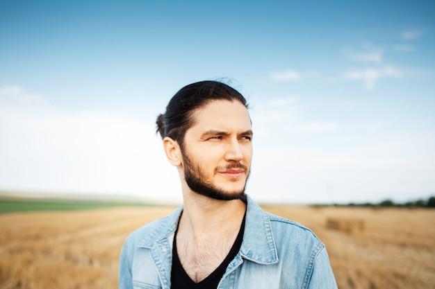 Portrait de jeune homme confiant sur fond de ciel flou et champ de foin.