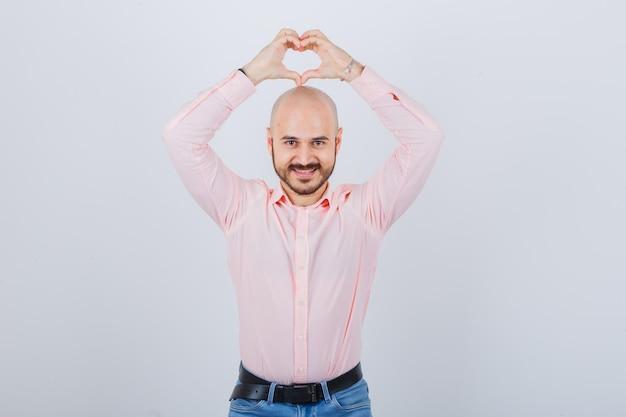 Portrait d'un jeune homme confiant montrant le geste du coeur