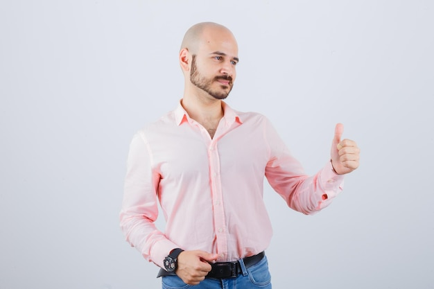 Portrait d'un jeune homme confiant montrant le geste du pouce vers le haut