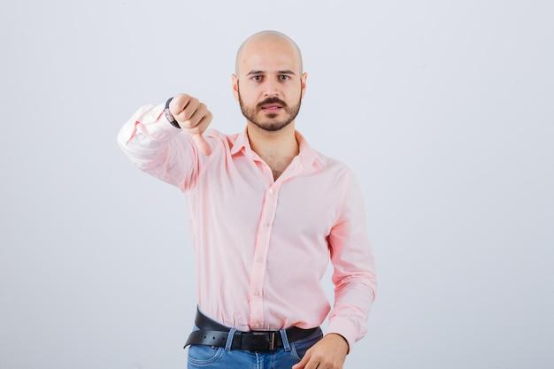 Portrait d'un jeune homme confiant montrant le pouce vers le bas
