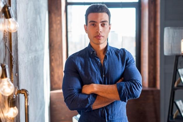 Portrait d'un jeune homme confiant avec ses bras croisés en regardant la caméra