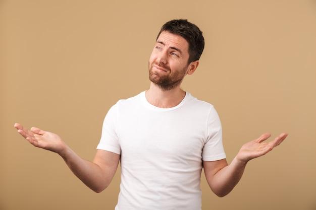 Portrait d'un jeune homme confus habillé avec désinvolture debout isolé