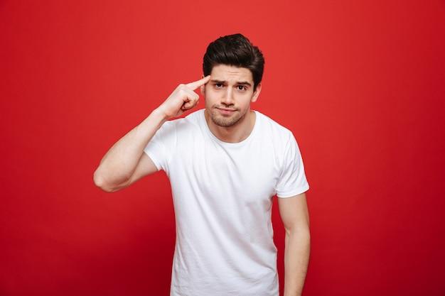 Portrait d'un jeune homme confus en t-shirt blanc