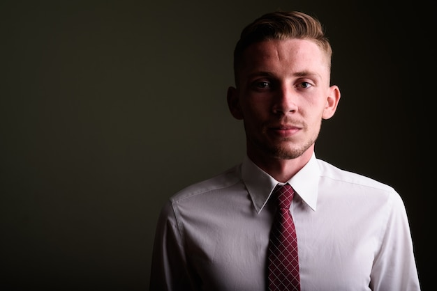 Portrait de jeune homme contre un mur de couleur
