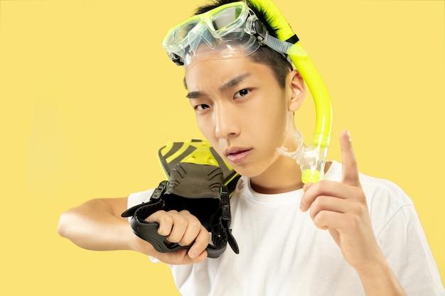 Portrait de jeune homme coréen. modèle masculin en chemise blanche et lunettes. tenant des palmes. concept d'émotions humaines, expression, été, vacances, week-end.