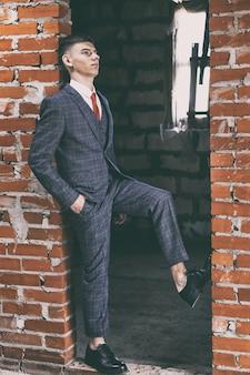 Portrait de jeune homme en costume classique et chaussures en cuir verni noir se penchant dans la porte du mur de briques brunes, tonique