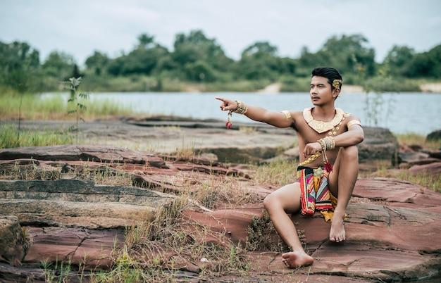 Portrait de jeune homme en costume traditionnel posant dans la nature en thaïlande