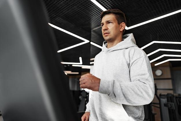 Portrait d'un jeune homme en coupe-vent orange séance d'entraînement sur une machine de fitness au gymnase