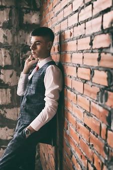 Portrait de jeune homme dans un élégant costume à la mode appuyé contre un mur de briques brunes, tonique