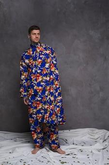 Portrait, de, a, jeune homme, dans, floral, usure, debout, contre, mur gris, regarder loin