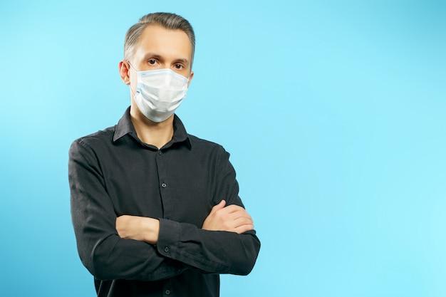 Portrait d'un jeune homme dans un masque médical de protection avec les bras croisés sur bleu