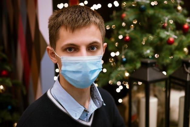 Portrait d'un jeune homme dans un masque médical et un pull sur fond de bokeh et un arbre de noël