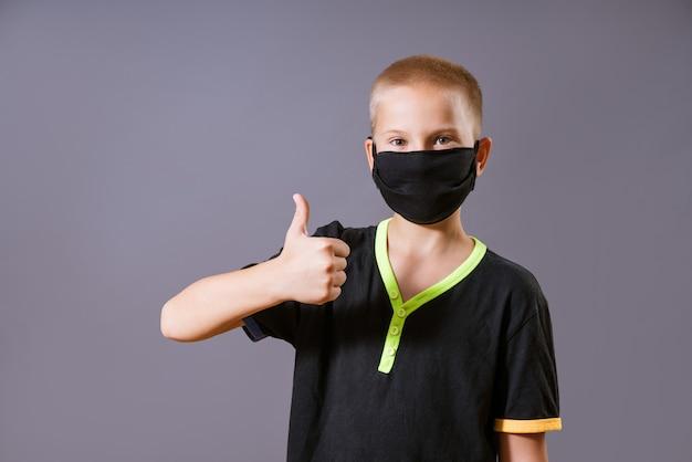 Portrait d'un jeune homme dans un masque noir montre un geste de la main que tout va bien sur un mur gris