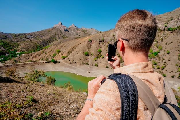 Portrait d'un jeune homme dans les montagnes près d'un lac de montagne aux couleurs vives de l'eau