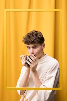 Portrait de jeune homme dans une scène jaune derrière un cadre