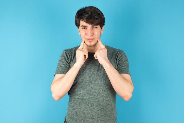 Portrait d'un jeune homme debout contre le bleu.