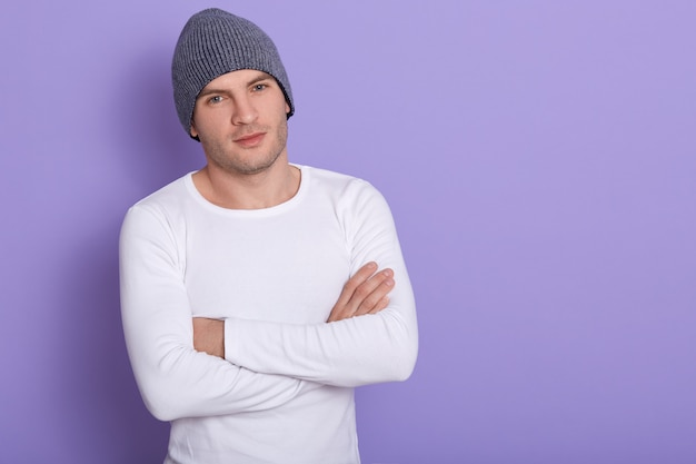 Portrait de jeune homme debout, les mains jointes sur le lilas, mâle attarctif portant une chemise blanche à manches longues et un bonnet gris. copiez l'espace pour le texte publicitaire ou promotionnel.