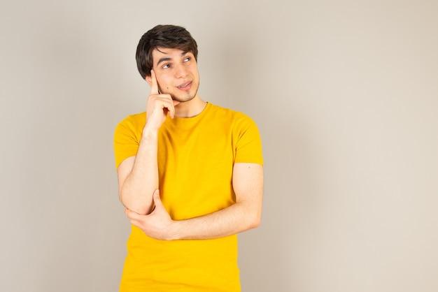 Portrait d'un jeune homme debout et posant contre le gris.