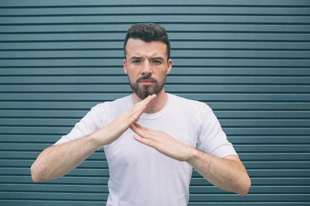 Portrait de jeune homme debout et posant. il montre le signe suffisant avec les mains. guy regarde la caméra. isolé sur rayé