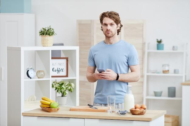 Portrait de jeune homme debout près de la table de cuisine avec téléphone mobile