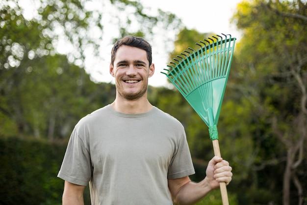 Portrait de jeune homme debout avec un râteau de jardinage dans le jardin
