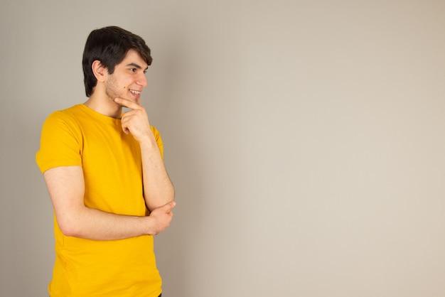 Portrait d'un jeune homme debout et regardant loin contre le gris.