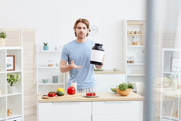 Portrait de jeune homme debout à la table avec des légumes frais et pointant sur une bouteille avec une bonne nutrition