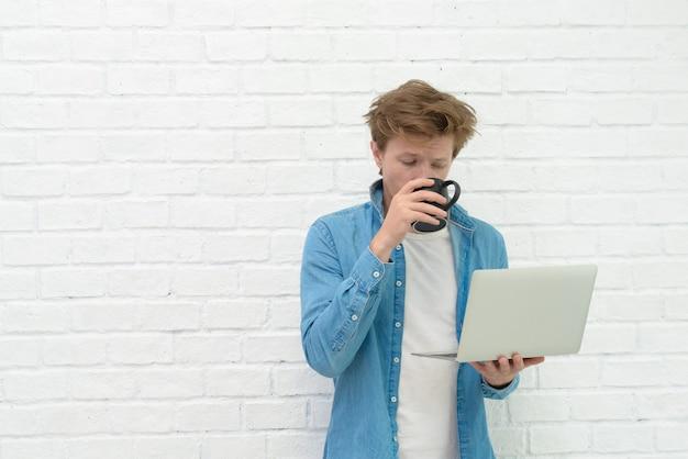 Portrait de jeune homme debout, tenant un ordinateur portable et boire un café avec un sourire heureux