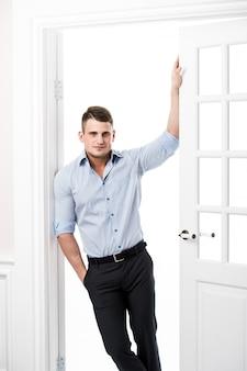 Portrait jeune homme décontracté appuyé contre le cadre d'une porte ouverte sur fond clair, souriant et regardant la caméra avec la main dans sa poche