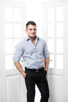 Portrait jeune homme décontracté appuyé contre le cadre d'une porte ouverte sur fond clair, souriant et regardant la caméra avec la main dans ses poches