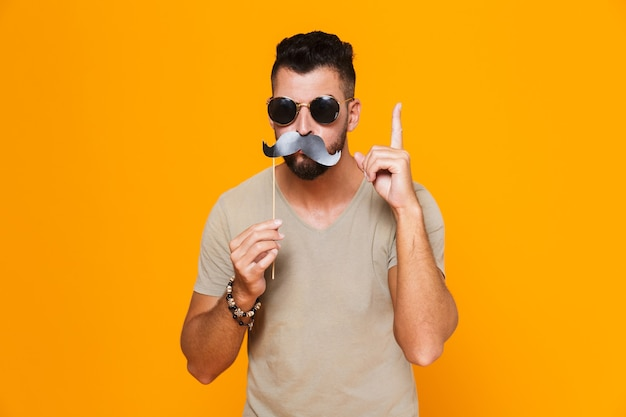 Portrait d'un jeune homme décontracté gai à lunettes de soleil