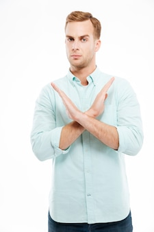 Portrait d'un jeune homme décontracté montrant un geste d'arrêt avec les bras croisés isolé sur un mur blanc