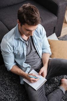 Portrait d'un jeune homme décontracté prenant des notes dans un cahier tout en étant assis sur le tapis à la maison