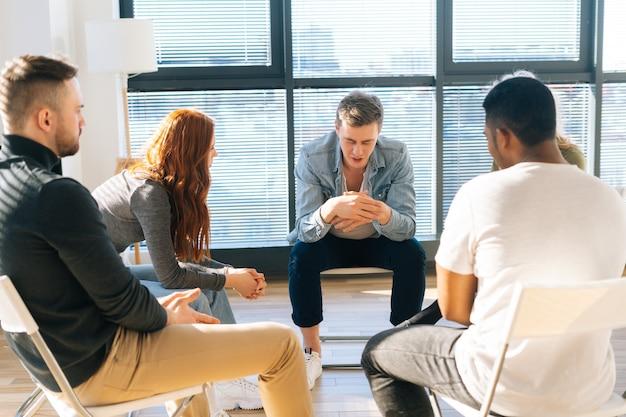 Portrait d'un jeune homme déprimé racontant son problème mental ou sa dépendance à d'autres patients assis en cercle. concept de consultation de groupe d'un problème de santé mentale avec un psychologue professionnel.